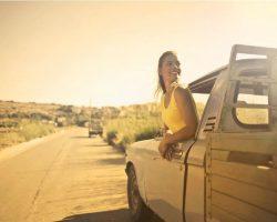 Frau in gelbem Top lehnt aus Autofenster