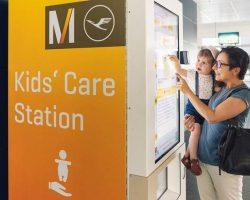 Flughafen Muenchen: Mutter mit Kid auf dem Arm am Automat